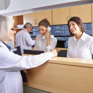21380363 - senior doctor talking with receptionist at hospital reception